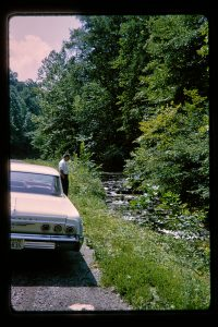 old car parked by a creek