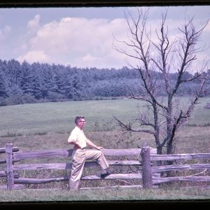 man at a split rail fence