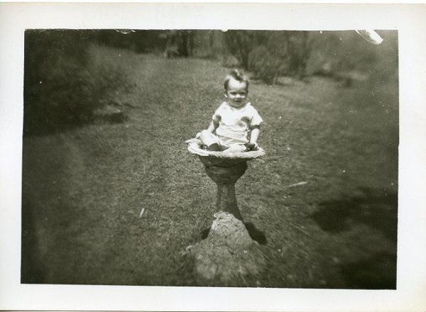 Little boy sitting in a bird bath 1940s