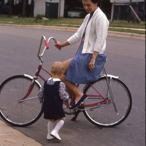 woman on bike talking to toddler, June 1972