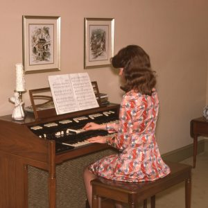 girl playing an organ in a living room 1-26-75
