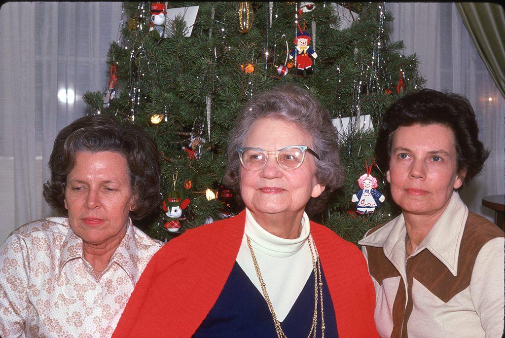 three women at a christmas tree