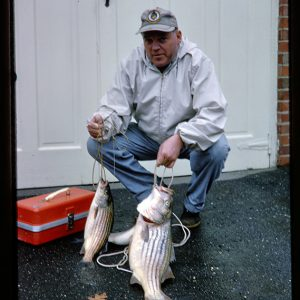 fisherman with fish in a driveway